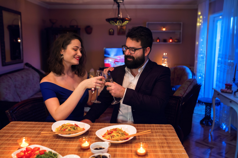 A formally dressed couple holds up wine glasses in their living room