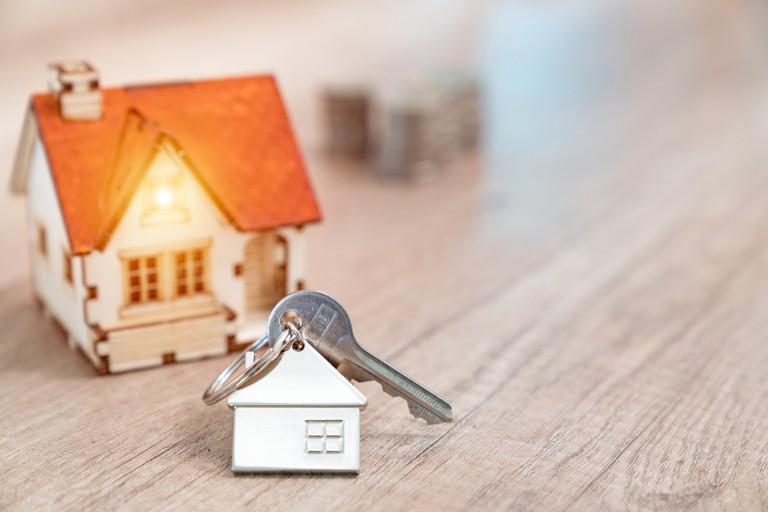 A house key on a house-shaped keychain