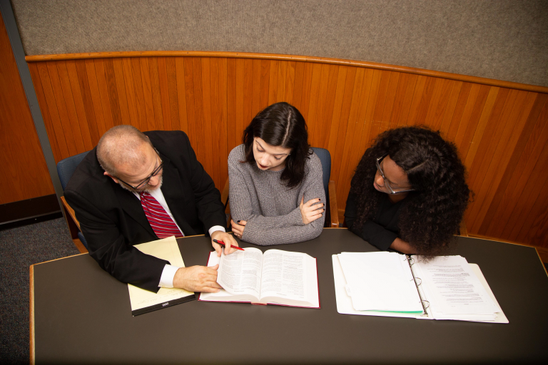 An attorney and two students review documents