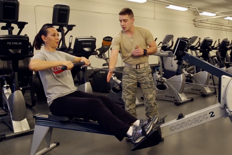 Woman working out on rowing machine with instructor