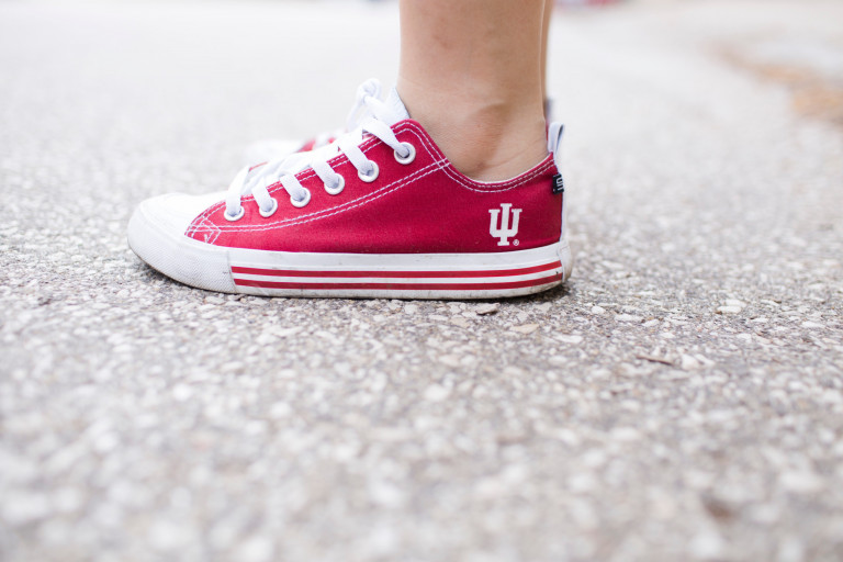 A foot wearing a red sneaker with an IU trident on it