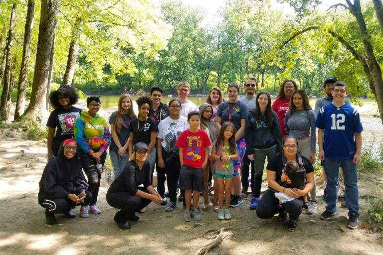 A large group of students from the Fostering Success Program stand by a wooded river.