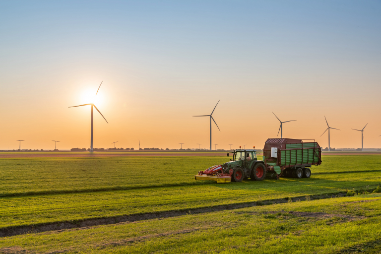 Tractor harvesting on an agricultural field with wind turbines in the background