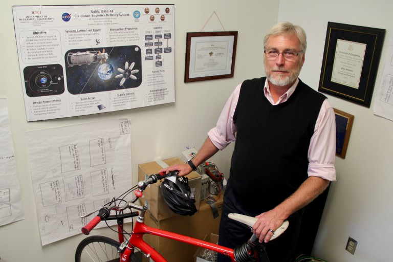 Peter Schubert stands with his bicycle in his office next to a NASA poster