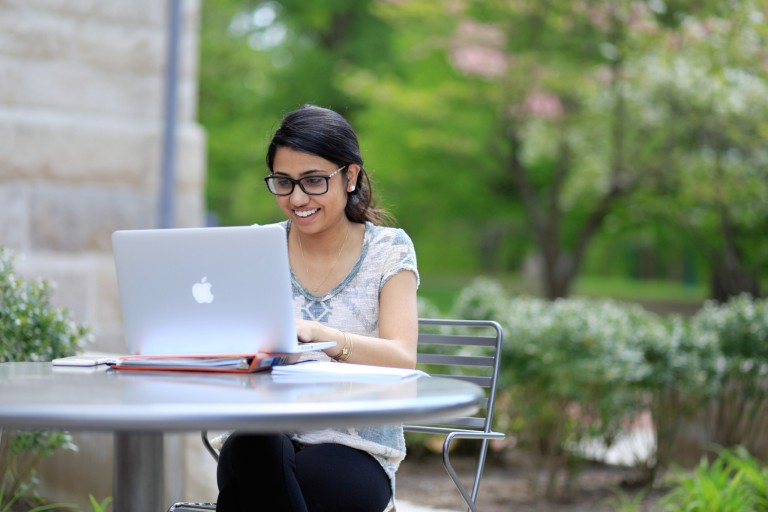 A student works on her computer outside