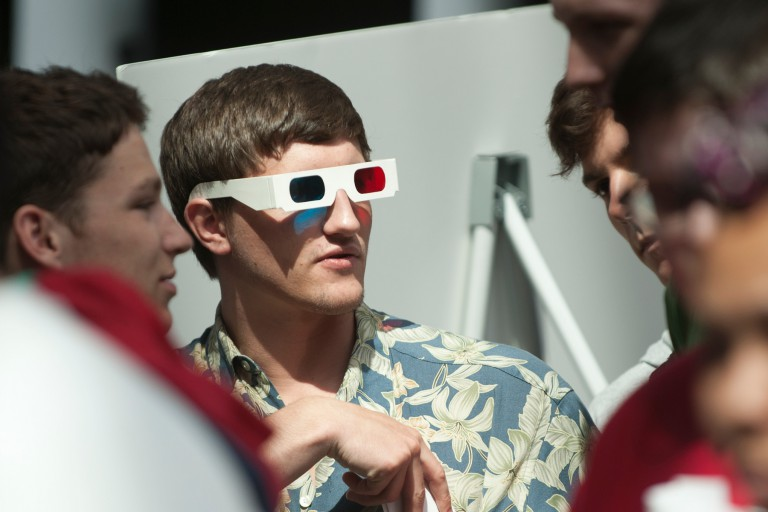 A student wears 3D glasses to observe another student's creation