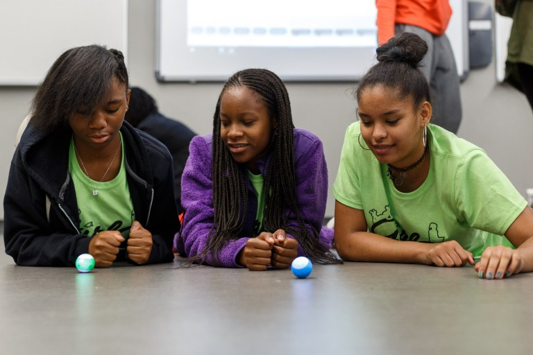 STEM summer campers watch their mini robots roll.