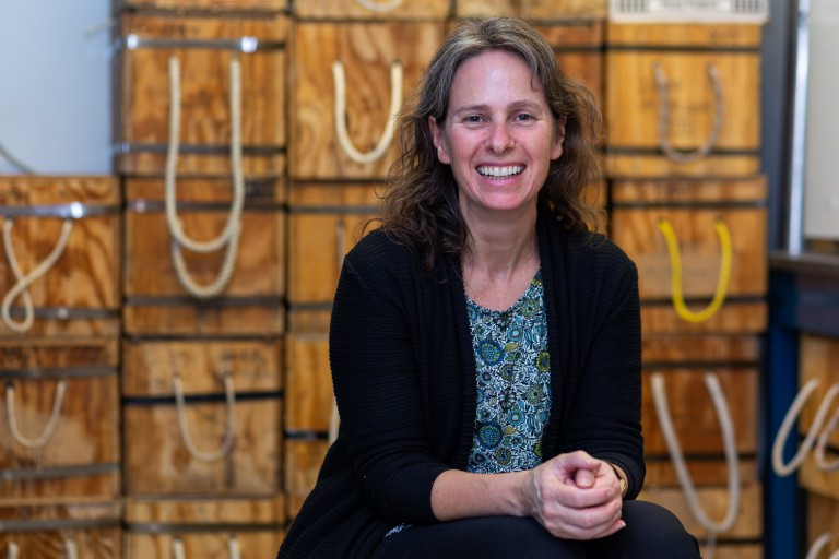 Geology professor Kathy Licht smiles at the camera, she is sitting in front of wooden boxes