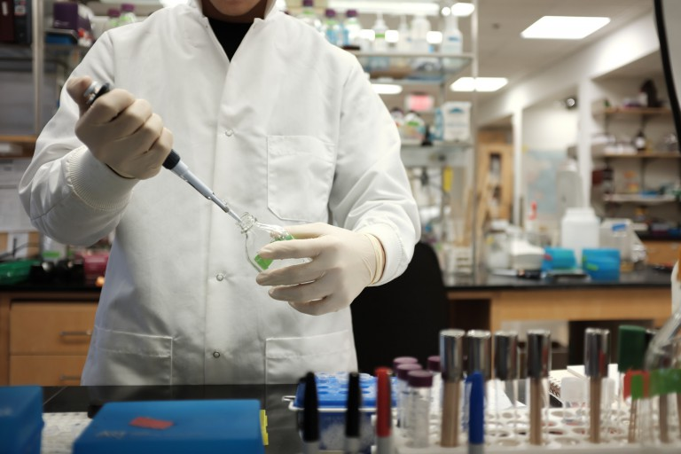 Scientist in a white lab coat filling a bottle