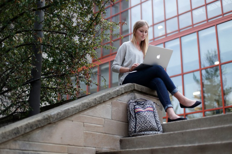 A girl sits on her laptop outside of Jordan Hall at IU Bloomington