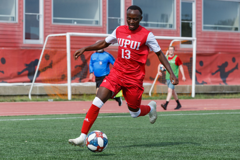 an IUPUI soccer play dribbles the ball during a match