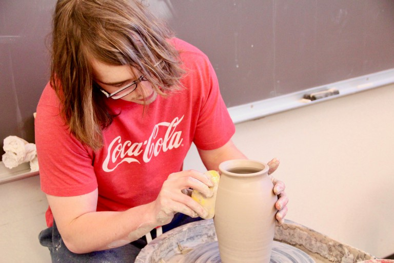 Senior John Buschbacher creates a vase on a pottery kick wheel during a summer ceramics class.