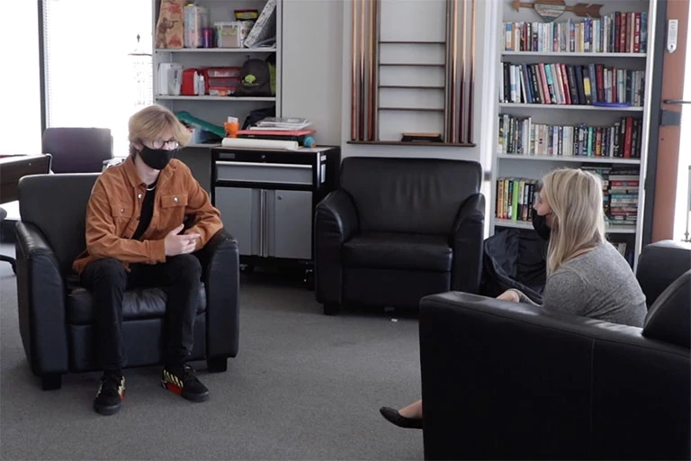 Two individuals wearing masks sit in chairs across from each other in an office