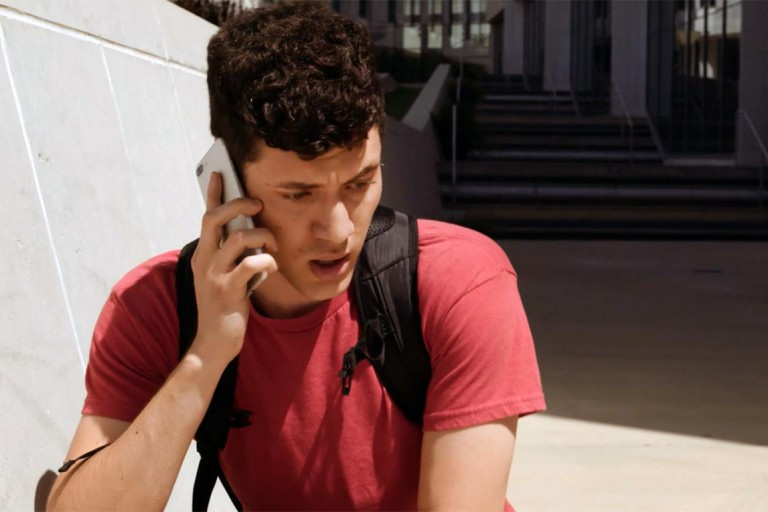 A video still of a student on his phone