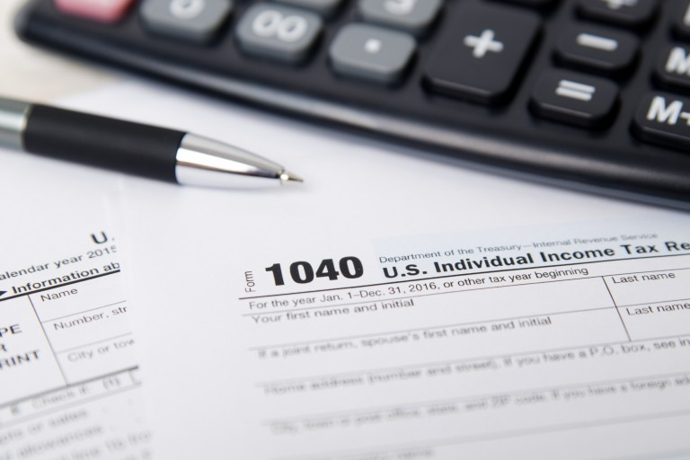 1040 tax form with a pen