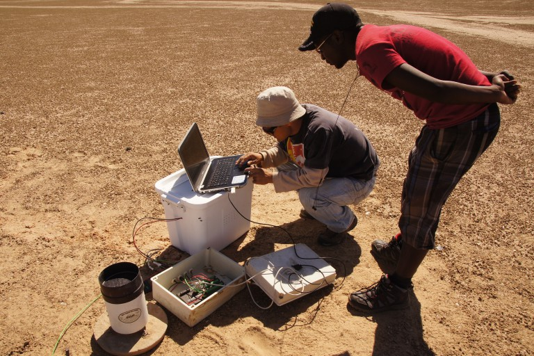 Lixin Wang kneels in Namib Desert to check the computer
