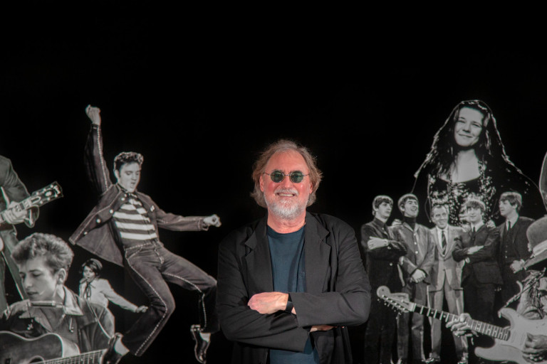 Glenn Gass with images of rock stars behind him
