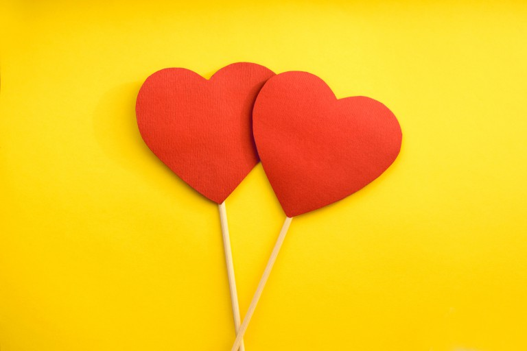 Two paper hearts against a yellow background