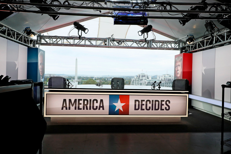 A TV news set with a chyron that reads 'American Decides'