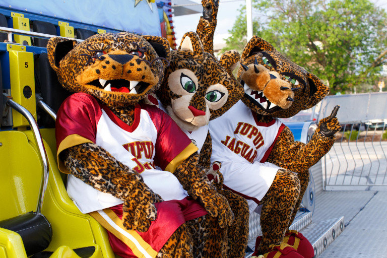 three jaguar mascots, Jinx, Jazzy and Jawz all sit on a carnival ride