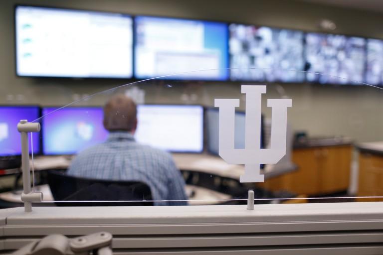 A man monitoring a large bank of computer screens