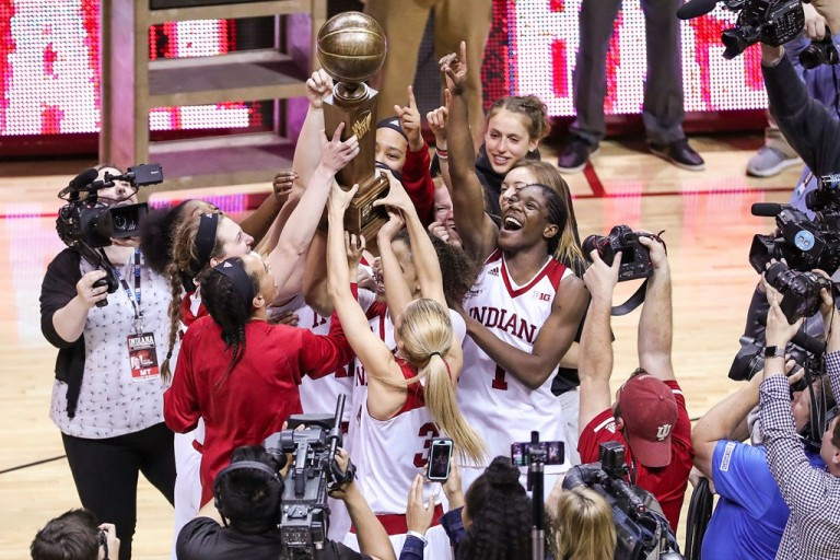 The IU women's basketball team gathers to hold up their WNIT championship trophy