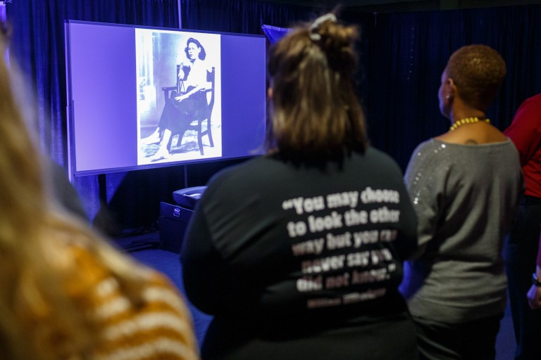 Tunnel of Oppression visitors view a video about a woman who faced oppression in Puerto Rico
