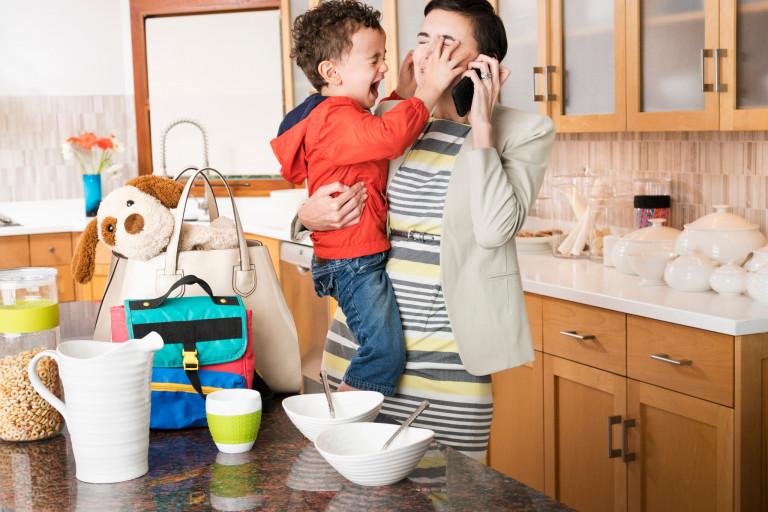 Mom holding her fussy child while multitasking