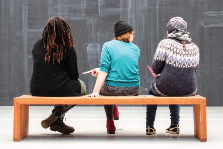 Three women sit on a bench with their backs to the viewer looking at a blank slate.
