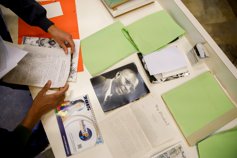 Hands unpack a photograph, movie poster and other documents