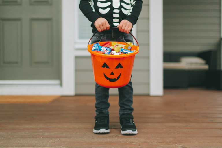 A boy holding a bucket full of candy