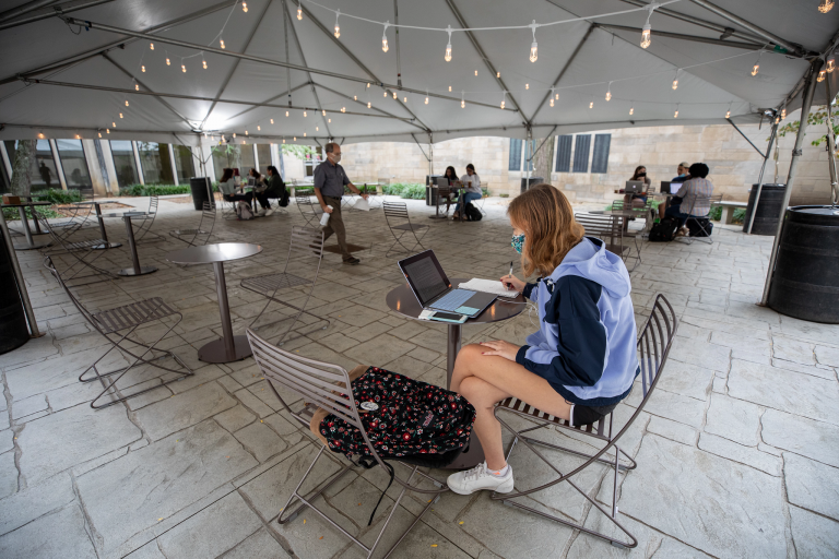 a masked female studies with a laptop under a tent