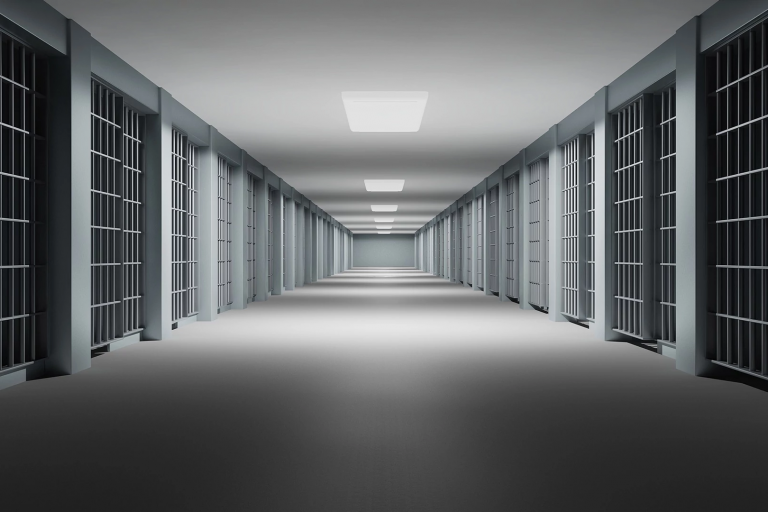 Empty prison corridor with jail cells on either side