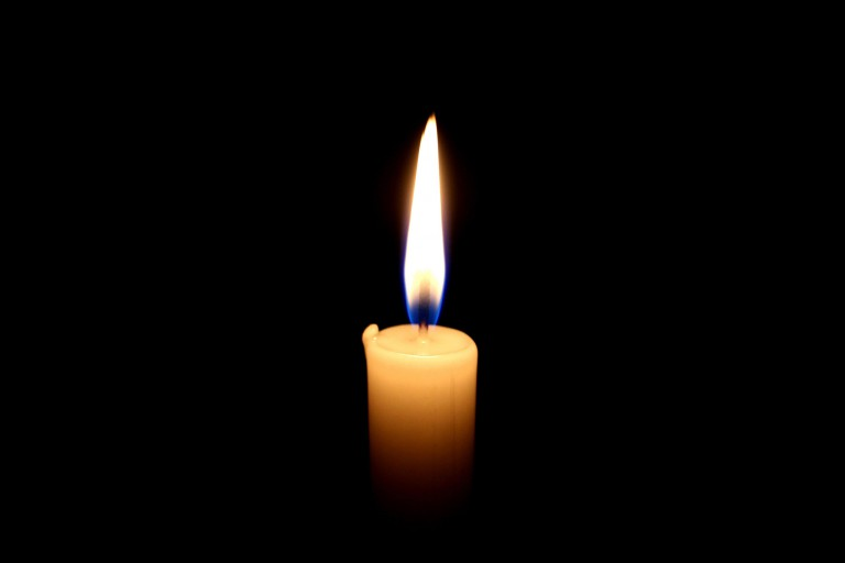 A candle burning in front of a black background