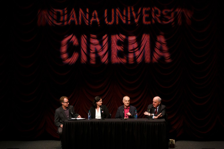 Several panelists sit on the stage at IU Cinema