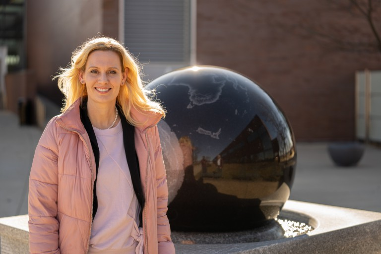 Julie Goodspeed-Chadwick posing in front of a round sculpture outside of a building
