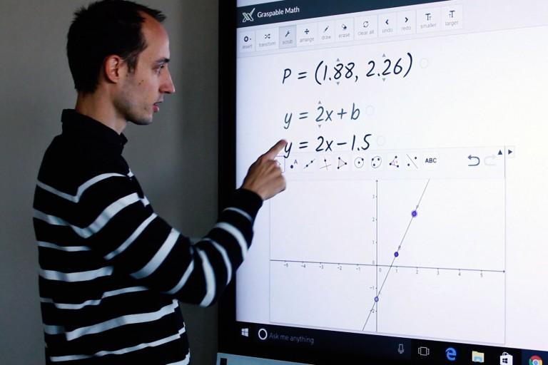 Man touches a white TV screen filled with algebraic equations and graphs