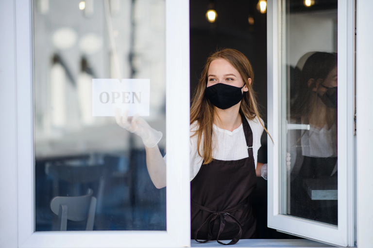 Woman wears a mask and puts an open sign in the window of her business