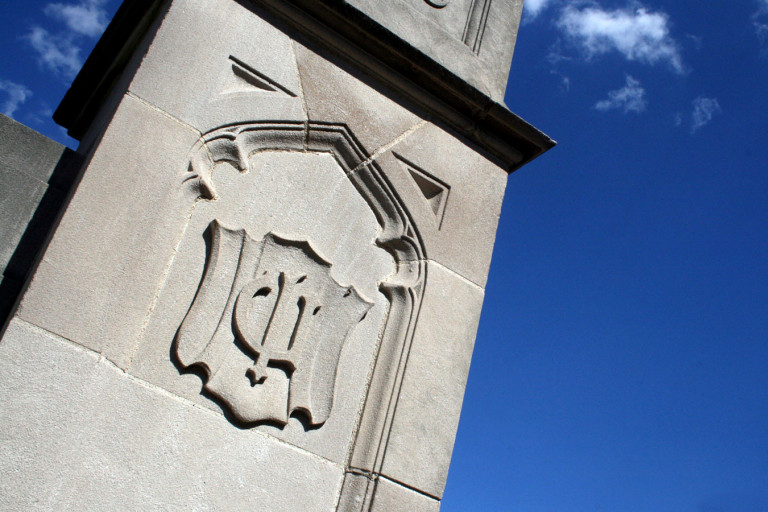 IU limestone crest in front of a bright blue sky