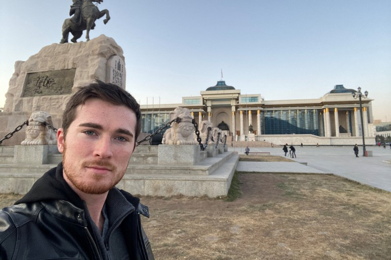 Brandon Boynton stands in front of Mongolia's Government Palace