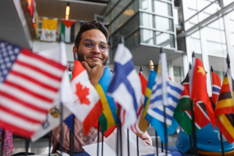 a student poses behind a row of flags sitting at a table