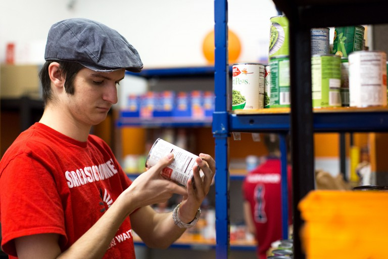A man looks at canned goods in the food pantry.