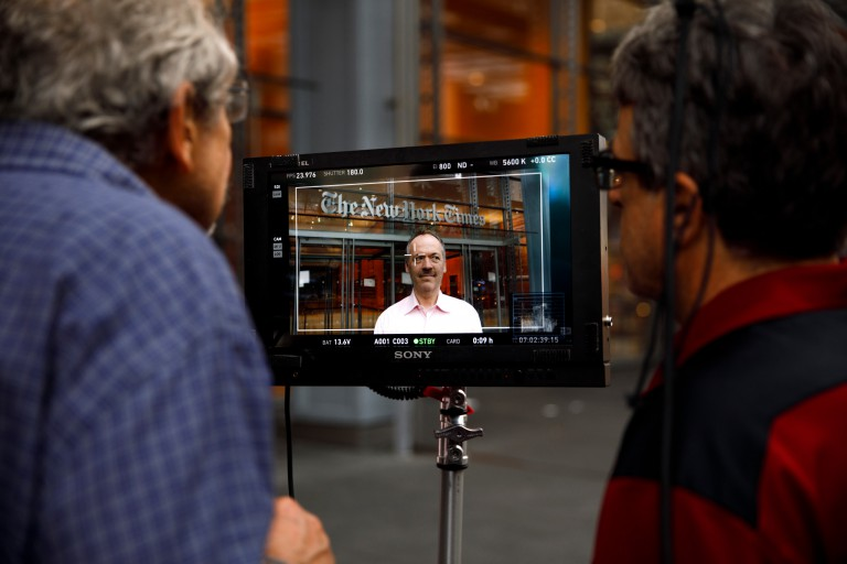 Will Shortz on a camera screen in front of the New York Times building.