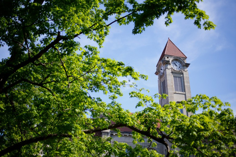 A limestone clocktower surrounded by trees on the IU Bloomington campus.