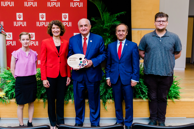 Michael A. McRobbie, Laurie McRobbie and Nasser Paydar pose with two IUPUI students.