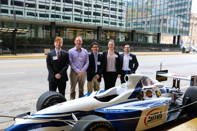 David Pierce stands with students next to race car
