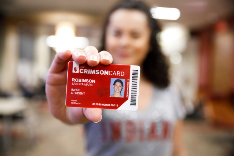 Student holds up a CrimsonCard