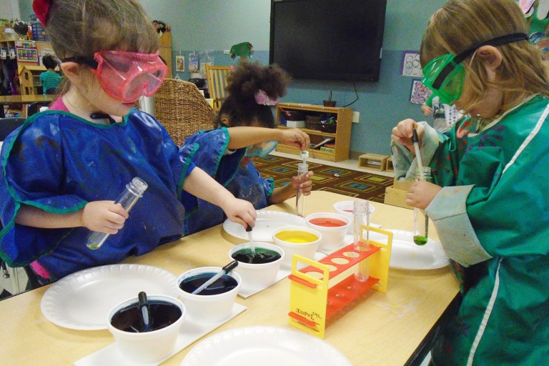 Children with goggles on experiment with paint at the Center for Young Children