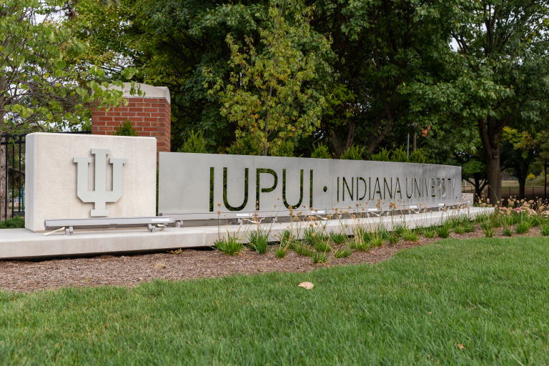 The IUPUI gateway, with a limestone IU trident and a metal sign reading 'IUPUI' 'Indiana University'