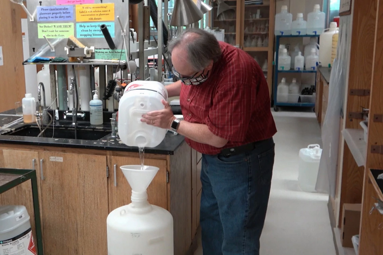 A man in a red plaid shirt pours chemicals for hand sanitizer into a large white container.